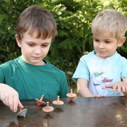 boys playing with wooden spinning tops