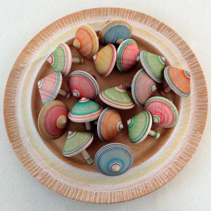 colourful spinning tops in a wooden bowl