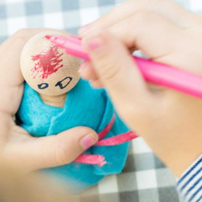 girl making a peg doll