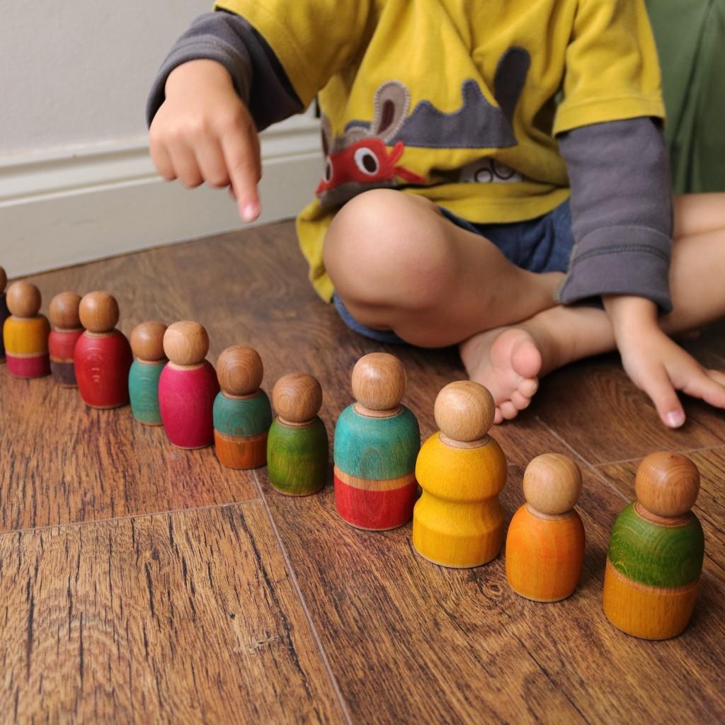 boy counting colourful peg dolls