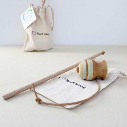 spinning top with string in a cotton bag