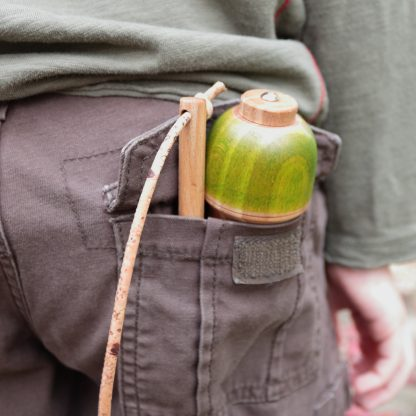boy carrying large wooden top in his back pocket
