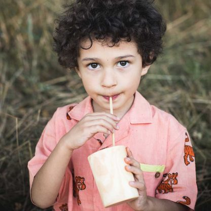 boy drinking from wood cup using a wheat straw