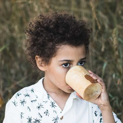 boy drinking from a wood cup