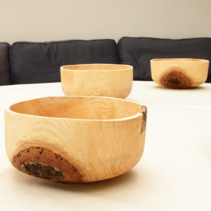 wooden bowls with bark on on a table