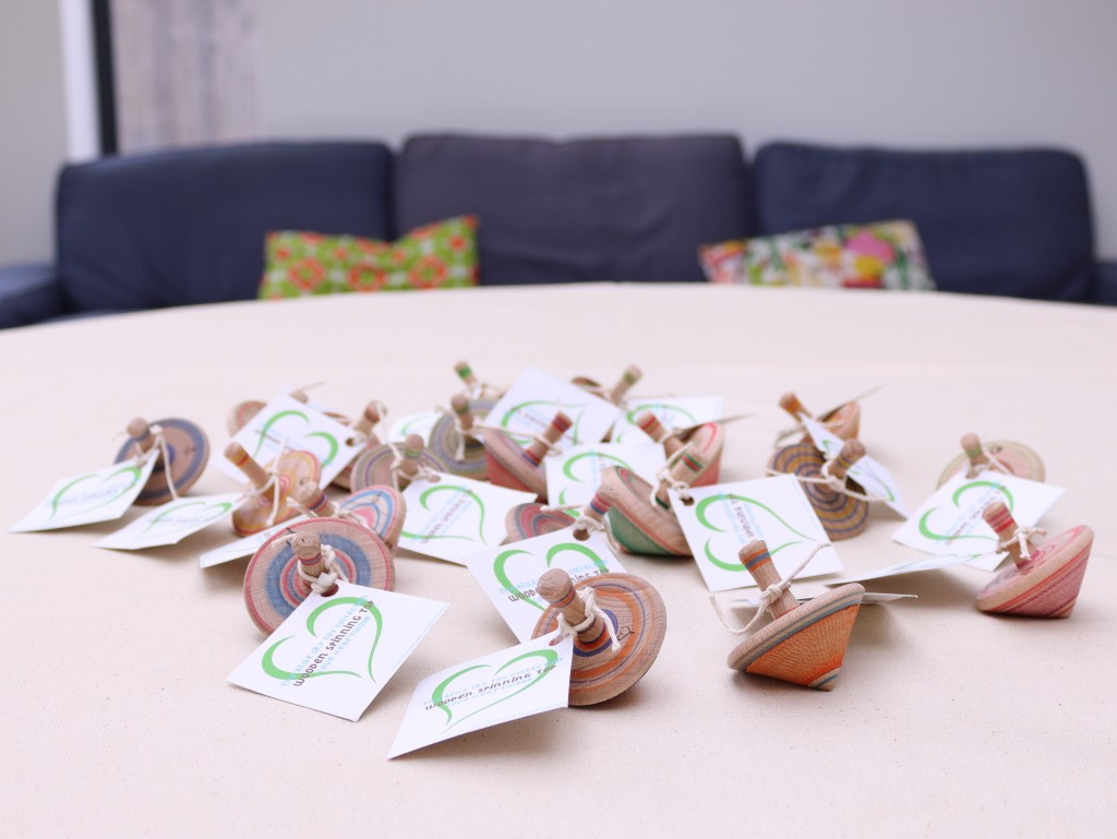 handmade wooden spinning tops with recycled paper tags.