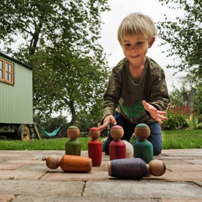 boy playing with wooden skittles