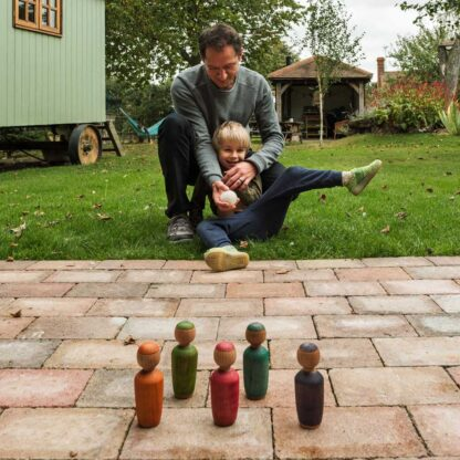 father and son playing with wooden skittles